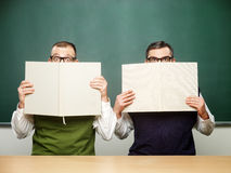 Male nerds covered faces with books stock photo
