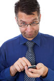 Male nerdy geek understands nothing from his phone Royalty Free Stock Photography