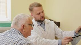 Male neurologist looking at an x-ray picture with an elderly patient.