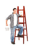 Male next to a ladder and holding a paint brush Royalty Free Stock Image
