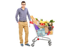 Male next to a shopping cart full with groceries. A young male posing next to a shopping cart full with groceries  on white background Royalty Free Stock Photography