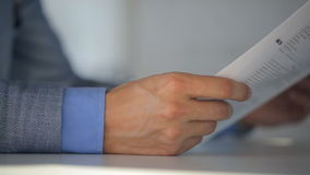 Male notary in suit jacket and light blue shirt holds a document and reads them while sitting at table, closeup. stock video footage
