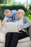 Male Nurse Assisting Senior Man In Using Laptop Stock Images