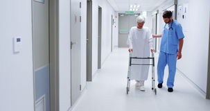 Male nurse assisting senior patient in using a walking frame stock footage