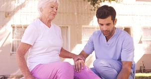 Male nurse assisting senior woman to exercise in the backyard stock video footage