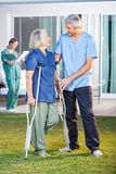 Male Nurse Assisting Senior Woman To Use Crutches. Full length of male nurse assisting senior women to use crutches with caretaker in background at nursing home Stock Photography