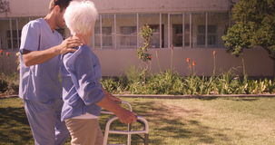 Male nurse assisting a senior woman to walk in garden stock footage
