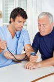 Male Nurse Checking Blood Pressure Of a Senior Man Stock Photo
