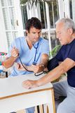 Male Nurse Checking Blood Pressure Of a Senior Stock Images