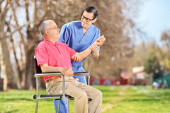 Male nurse checking the pulse of a senior Royalty Free Stock Photos