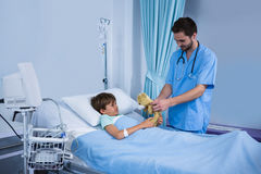 Male nurse giving teddy bear to patient during visit in ward Royalty Free Stock Image