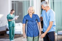 Male Nurse Helping Senior Woman To Use Crutches. Male nurse helping senior women to use crutches with caretaker in background at nursing home Stock Photography