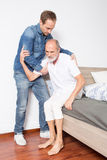 Male nurse helps man out of bed Royalty Free Stock Image