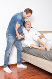 Male nurse helps man out of bed Stock Photos