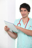 Male nurse holding chart. Male nursein scrubs holding chart Royalty Free Stock Photos