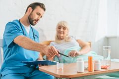 male nurse holding clipboard and pointing at pills to senior woman stock photo