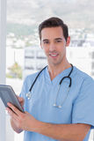 Male nurse holding a tablet pc. Cheerful male nurse holding a tablet pc Royalty Free Stock Images