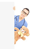 Male nurse holding teddy bear and standing behind blank panel Royalty Free Stock Images