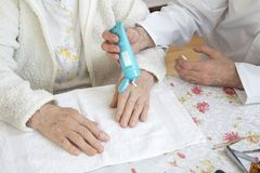 Male nurse puts the cream on the old woman`s hand. Cosmetic treatment and nursing. royalty free stock images