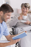 Male nurse reading a book to senior Royalty Free Stock Photography