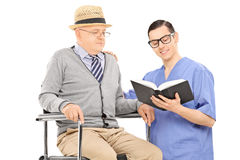 Male nurse reading to an elderly gentleman Royalty Free Stock Images