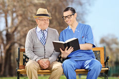 Male nurse reading to a pensioner in park Royalty Free Stock Images
