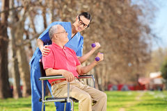 Male nurse and a senior lifting dumbbells in park Stock Image