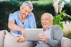 Male Nurse And Senior Man Laughing While Using Royalty Free Stock Images