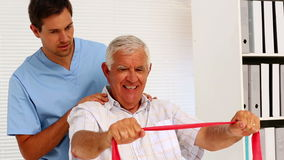 Male nurse showing elderly patient how to use resistance band Stock Photography