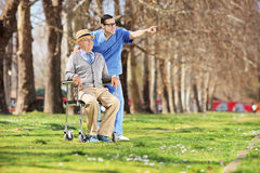 Male nurse showing something to man in wheelchair Stock Image