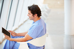 Male Nurse Sitting In Chair Using Digital Tablet Stock Images