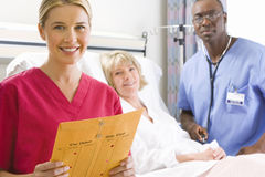 Male nurse with stethoscope by mature female patient in hospital bed, female nurse in foreground, smiling, portrait Royalty Free Stock Photo