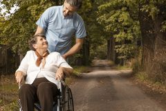 Nurse supporting smiling senior woman in the wheelchair while walking in the forest royalty free stock photos