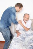 Male nurse takes care of older man in bed Stock Photography