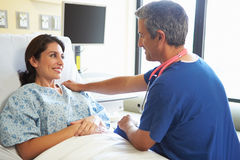 Male Nurse Talking With Female Patient In Hospital Room Stock Photo