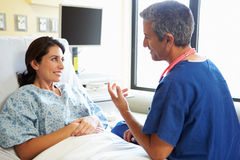 Male Nurse Talking With Female Patient In Hospital Room. Sitting Beside Wearing Scrubs Royalty Free Stock Photos