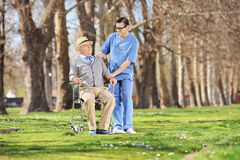 Male nurse talking to a senior man in the park Royalty Free Stock Images