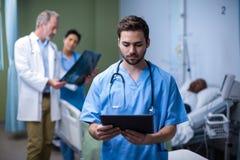 Male nurse using digital tablet in ward Royalty Free Stock Image