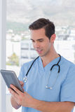 Male nurse working on a tablet pc. Smiling male nurse working on a tablet pc Royalty Free Stock Image