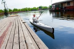 Male oarsman canoeing on lake using paddle in summer day. Entertainment on the lake. Low angle photo of man moored to the wooden shore after a boat ride and royalty free stock photos