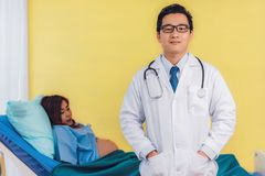 Male Obstetrician Doctor professionals with confidence and pregnant woman blurry background stock images