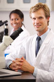 Male och kvinnliga forskare som använder mikroskop i laboratorium Arkivbild