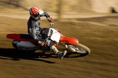 Male Off Road Biker Riding The Motor Bike. With speed on a race track Stock Photography