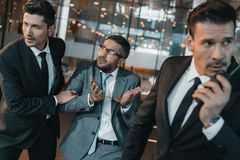 Male offender showing two young security guards shrug. Gesture stock photography