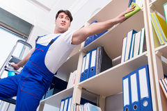 The male office cleaner cleaning shelves in office Stock Images