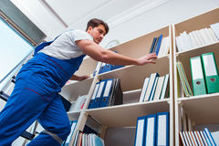 The male office cleaner cleaning shelves in office Stock Image