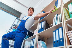 The male office cleaner cleaning shelves in office Stock Photography
