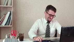 Male office manager with a beard and glasses, satisfied with the laptop. The morning of a working day in the office stock footage