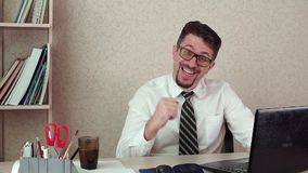 Male office manager with a beard and spectacles, success, good luck. With the laptop. The morning of a working day in the office stock video footage