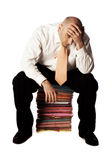 Male Office Worker. Balding man seated on stack of colorful files in white shirt and tie, head in hands, isolated on white background Royalty Free Stock Image